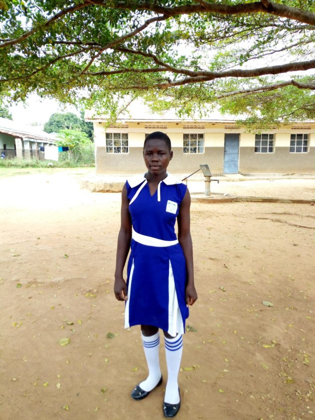 Joyce Awate standing in front of a school building